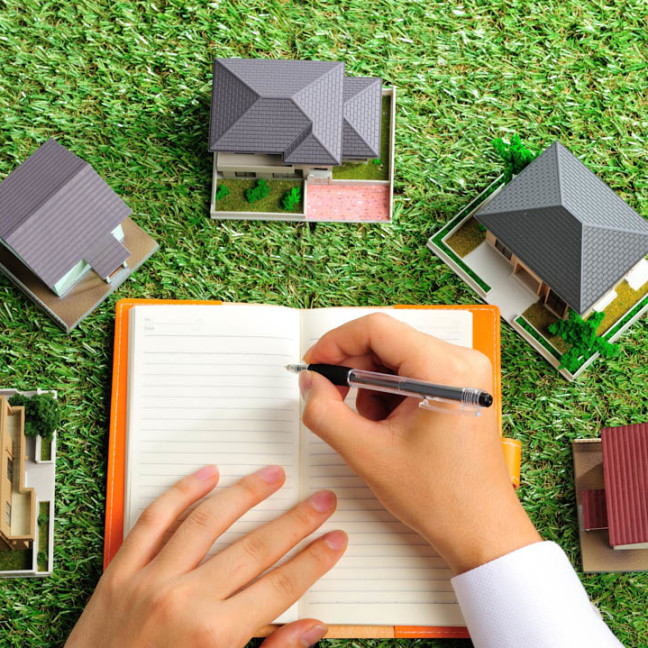 緑の芝生の上にたくさんの家が置いてあるビジ